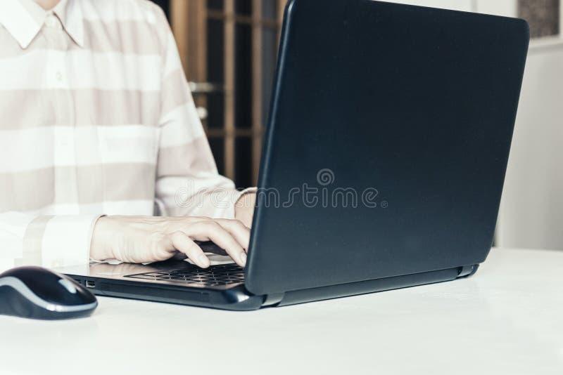 Nahaufnahme der Handfrau schreibend auf Tastaturlaptop auf weißer Tabelle, Geschäftskonzept stockbild