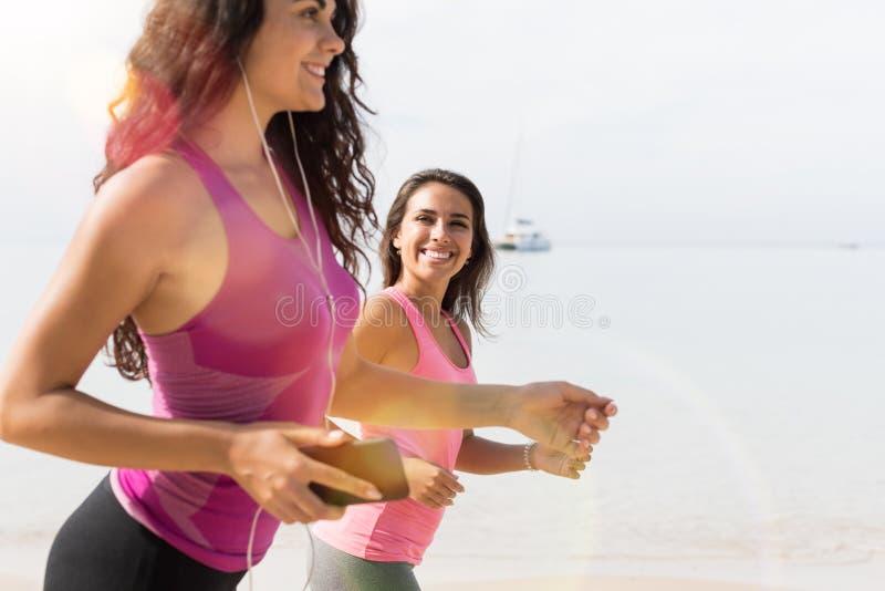 Nahaufnahme der jungen Frau zwei, die zusammen auf den Strand-attraktiven Mädchen laufen auf Küsten-Sport-Läufer-Eignungs-Trainin lizenzfreie stockfotos