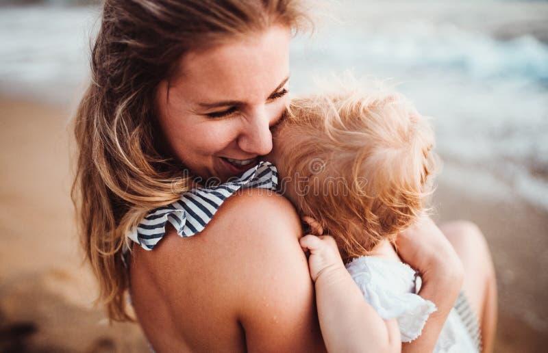 Nahaufnahme der jungen Mutter mit einem Kleinkindm?dchen auf Strand an den Sommerferien lizenzfreies stockfoto