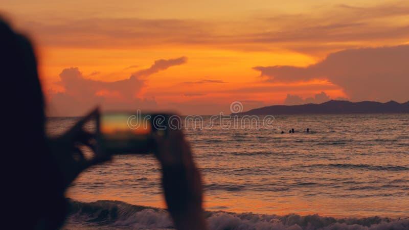 Nahaufnahme der jungen touristischen Frau fotografiert Meerblick mit Smartphone während des Sonnenuntergangs am Strand lizenzfreies stockbild