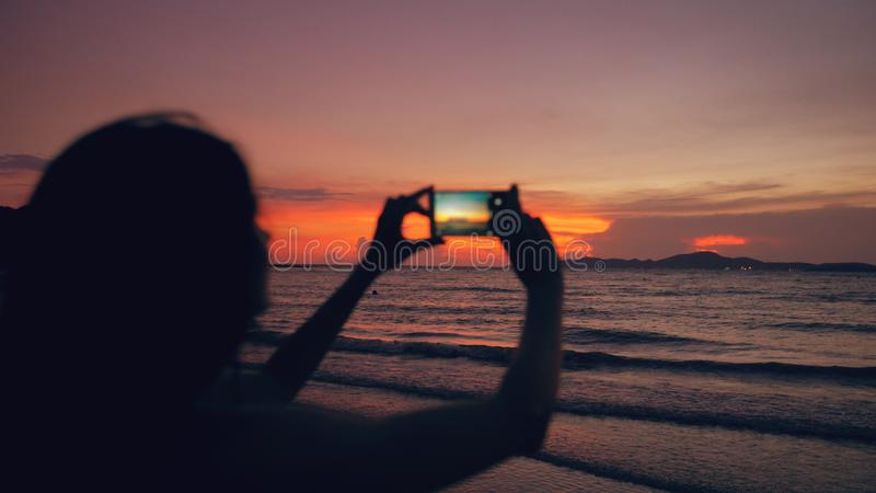 Nahaufnahme der jungen touristischen Frau fotografiert Meerblick mit Smartphone während des Sonnenuntergangs am Strand stockfoto