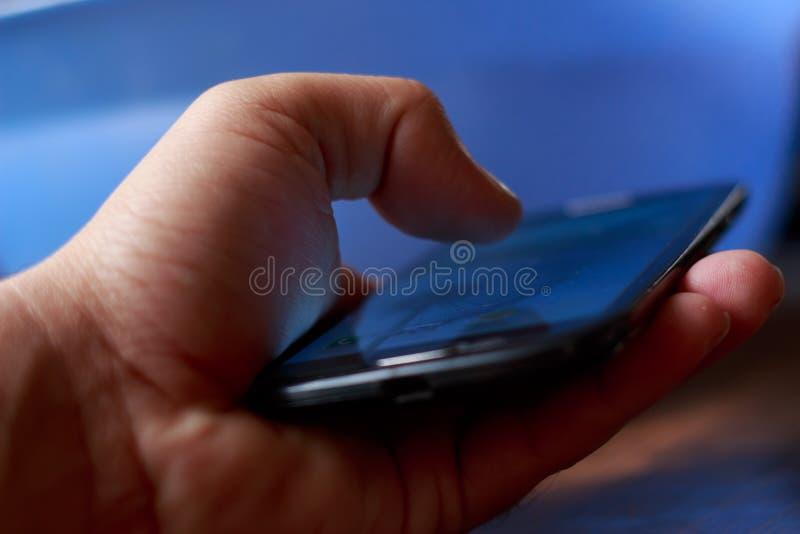 Nahaufnahme der Jungenhand unter Verwendung des Smartphone Blauer unscharfer Hintergrund lizenzfreie stockbilder