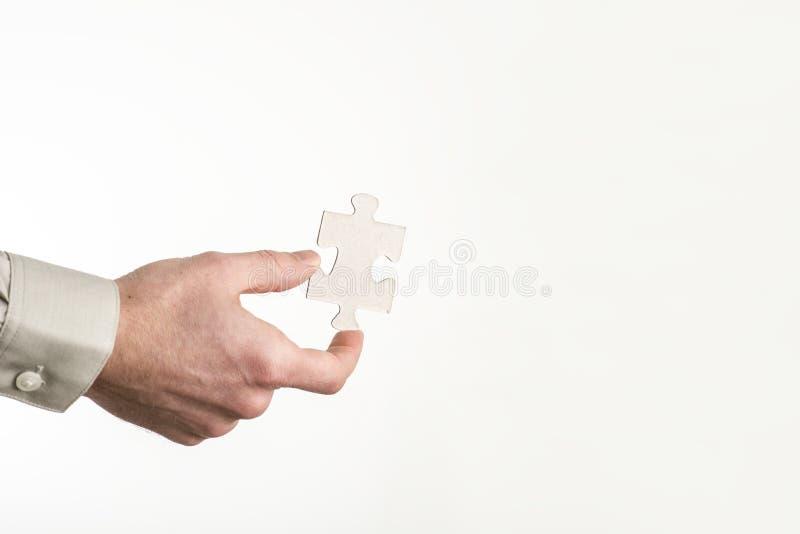 Nahaufnahme der männlichen Hand ein leeres Puzzlespielstück halten stockfoto