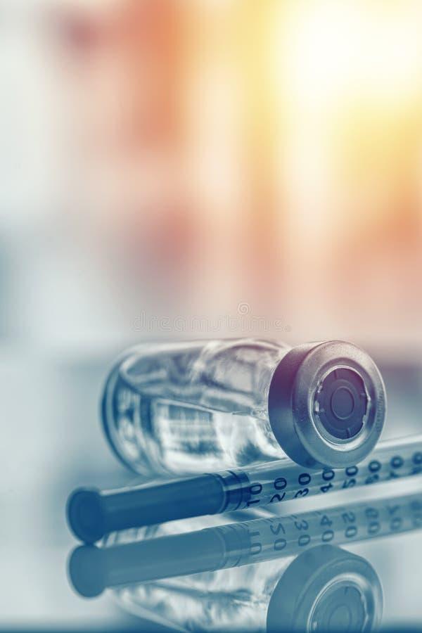 Nahaufnahme der Medizinphiole oder -grippe, der Masernimpfflasche mit Spritze und der Nadel für Immunisierung auf medizinischem H lizenzfreie stockfotos