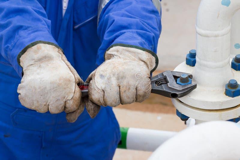 Nahaufnahme der menschlichen Handfestlegung und Halt lecken Flansch durch Schlüssel stockfotos