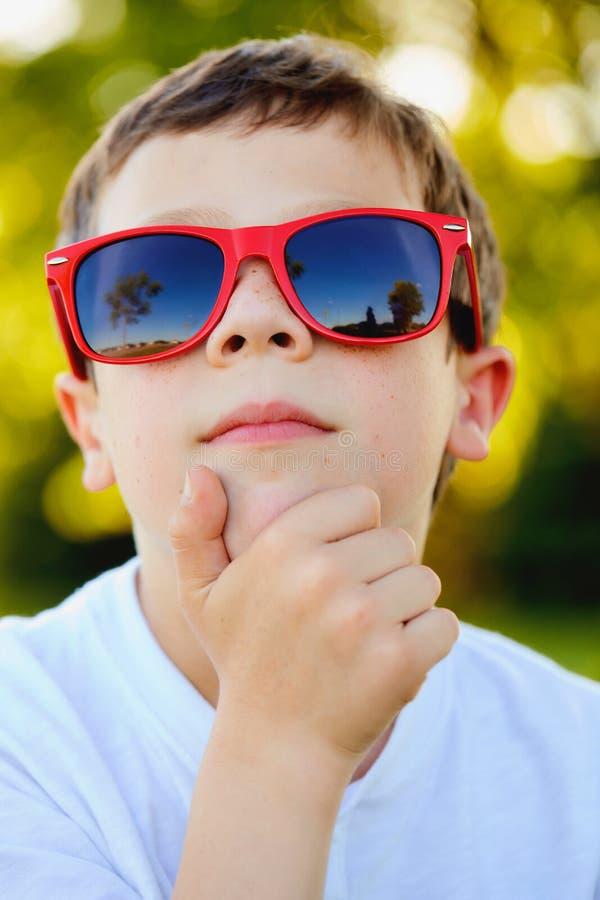 Nahaufnahme der nachdenklichen tragenden Sonnenbrille des kleinen Jungen stockbild