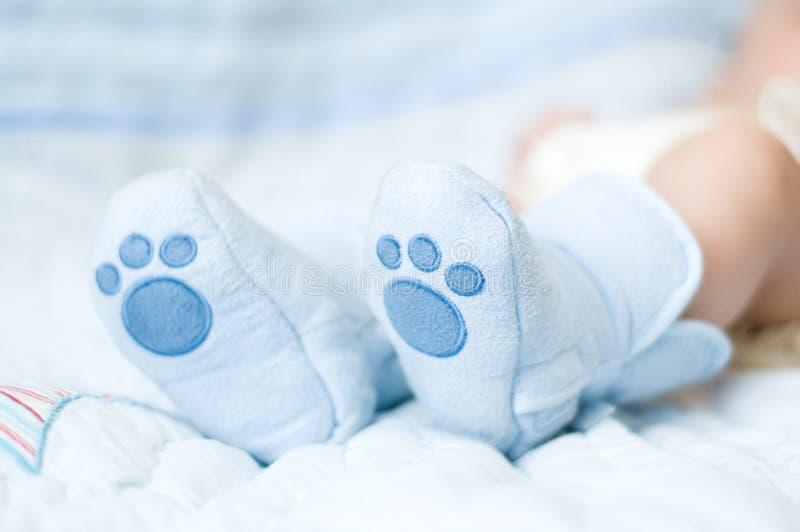 Nahaufnahme der neugeborenen Füße in den weichen blauen Beuten lizenzfreies stockfoto