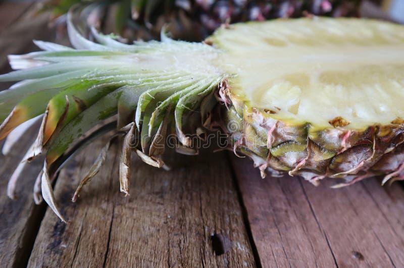 Nahaufnahme der offenen Ananas halb auf hölzernem Hintergrund stockbilder