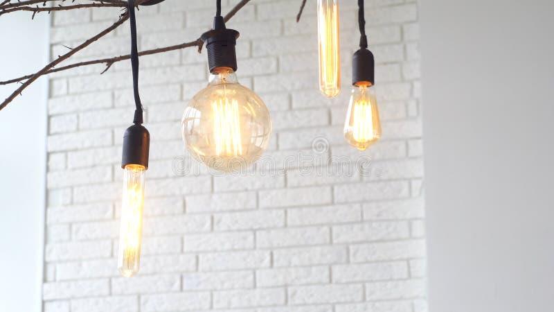 Nahaufnahme der Palme des Mannes gro?e Birne der elektrischen Lampe im hellen Raum gegen wei?e Backsteinmauer ber?hrend media ele stockfoto