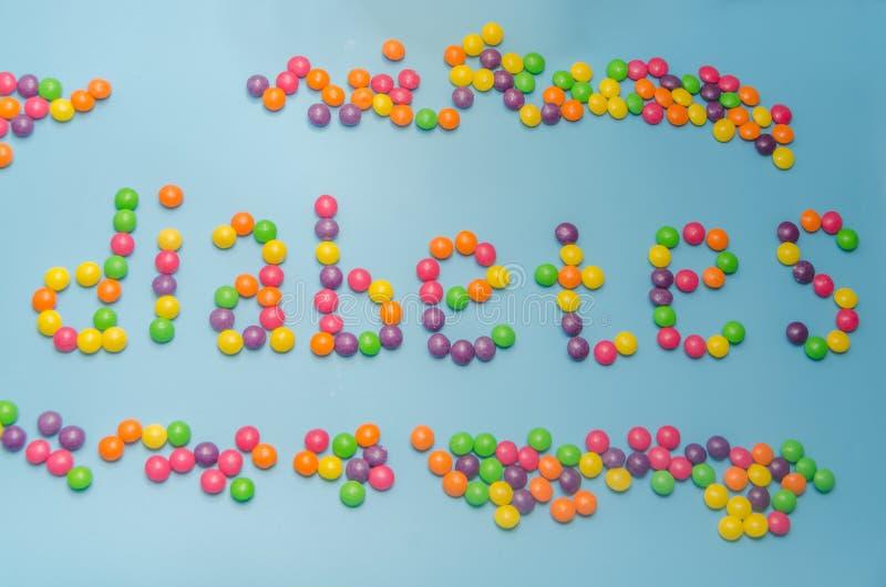 Nahaufnahme der Süßigkeit, Karamell zeichnete Wortdiabetes, auf blauem backgroun lizenzfreies stockbild