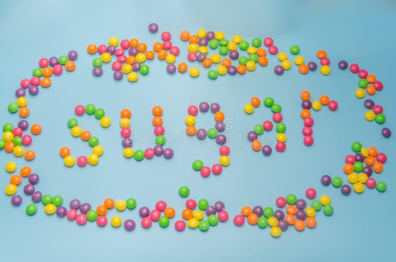 Nahaufnahme der Süßigkeitskaramel-Zuckerdiät ausgebreitet, auf blauem Hintergrund stockfotos