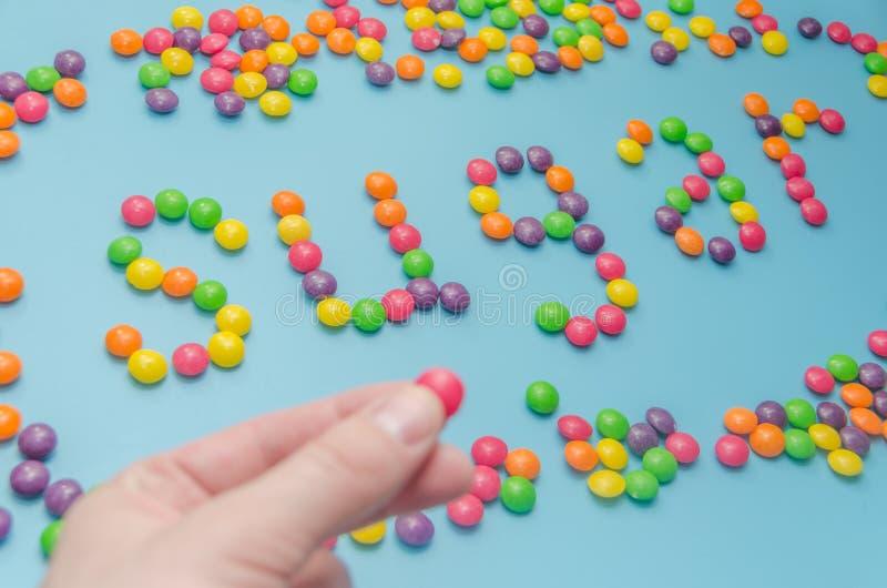 Nahaufnahme der Süßigkeitskaramel-Zuckerdiät ausgebreitet, auf blauem Hintergrund stockfotografie