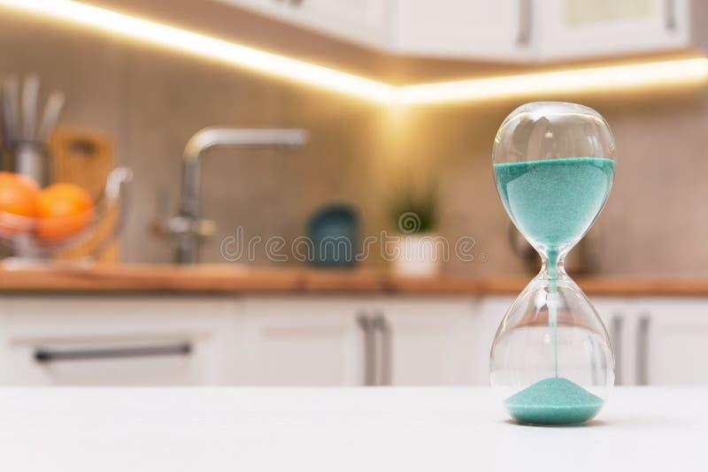 Nahaufnahme der Sanduhr auf einem weißen Holztisch mit defocus Küche stockbild