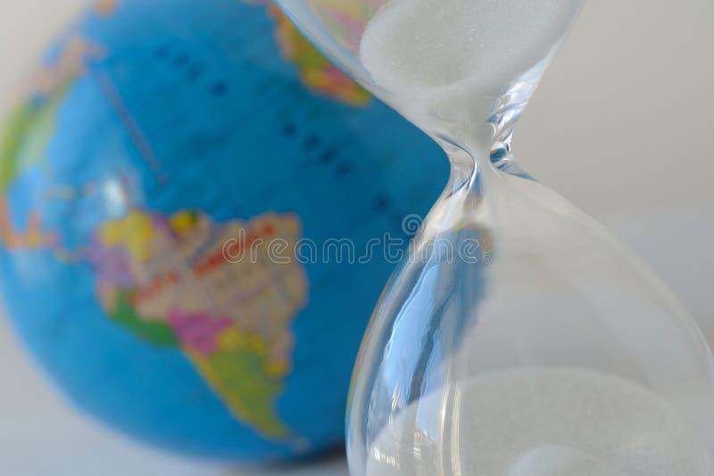 Nahaufnahme der Sanduhr mit Planetenerde im Hintergrund - Verschmutzung, Ökologie, globale Erwärmung, Klimawandelkonzept lizenzfreie stockfotos