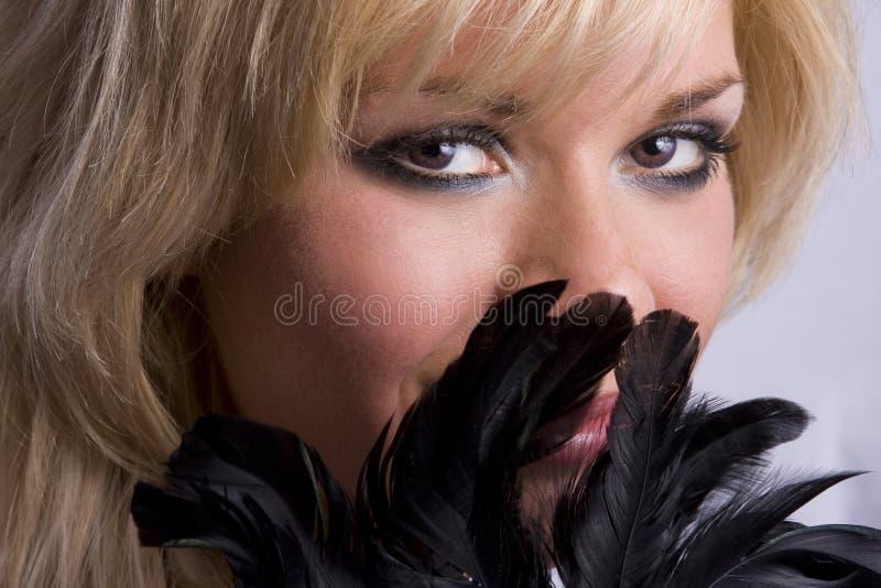 Nahaufnahme der schönen Frau mit schwarzer Feder lizenzfreie stockbilder
