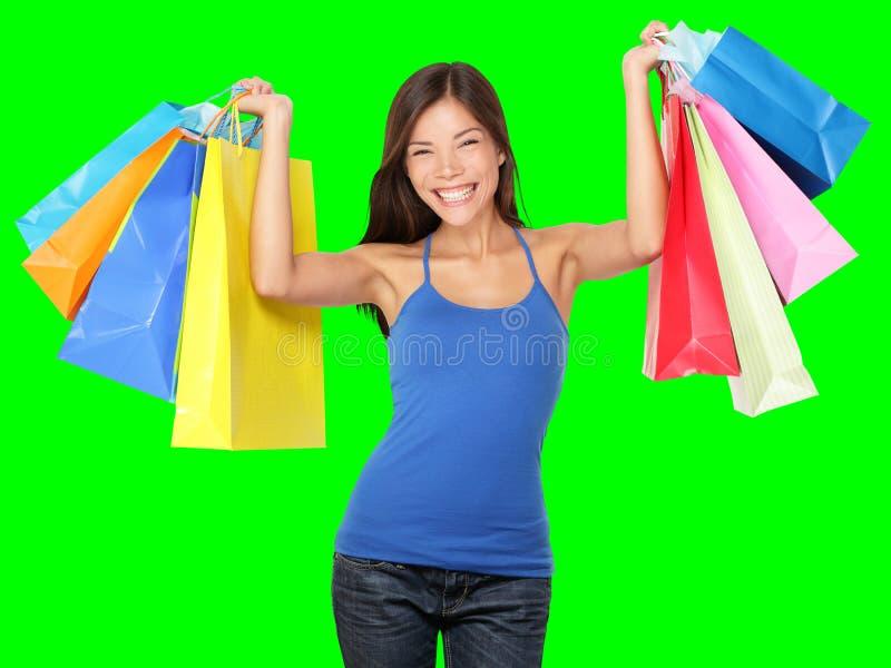 Nahaufnahme der schönen Frauenfahrwerkbeine in den roten hohen Absätzen und in den bunten Einkaufenbeuteln lizenzfreies stockbild