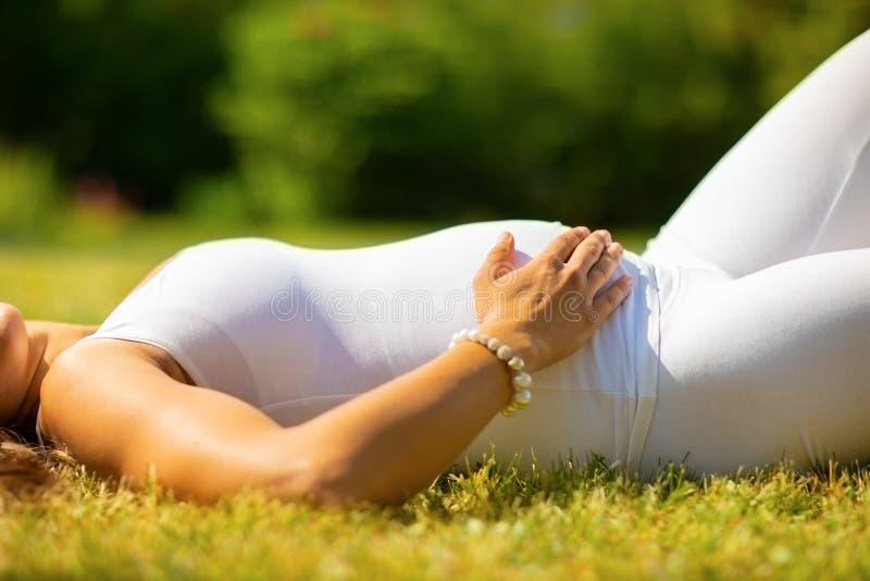 Nahaufnahme der schönen schwangeren Frau in der weißen Kleidung, die auf Gras legt stockfotografie