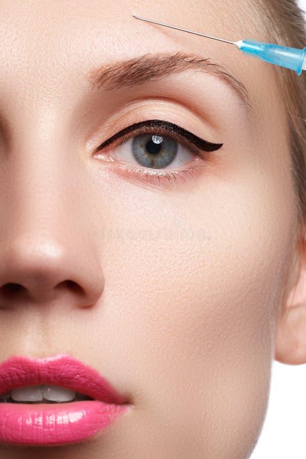 Nahaufnahme der Schönheit erhält Einspritzung Schönes Gesicht und die Spritze (Konzept der plastischen Chirurgie und der Kosmetik lizenzfreies stockbild