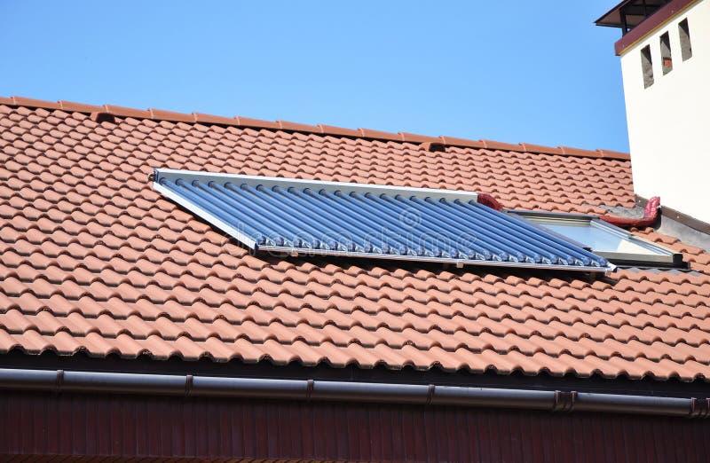 Nahaufnahme der Solarwasserflächenheizung auf rotem mit Ziegeln gedecktem Hausdach mit Oberlichtern und Dachfenster lizenzfreies stockfoto