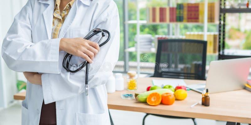 Nahaufnahme der Stellung des asiatischen Ernährungswissenschaftlerdoktorfrauen-Holdingstethoskops stockbild