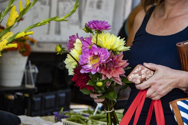 Nahaufnahme der unerkennbaren Frau mit Blumenstrauß von den schönen Blumen, die Handy und Einkaufstasche und Geldbeutel tragen lizenzfreie stockfotos