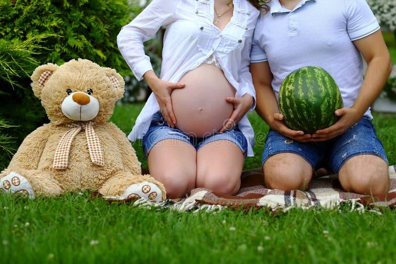 Nahaufnahme der unerkennbaren schwangeren Frau mit überreicht Bauch, einen Mann mit einer Wassermelone, ein Spielzeugweiche betre lizenzfreie stockfotos