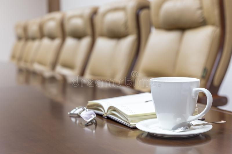 Nahaufnahme der weißen Kaffeetasse auf Tabelle im leeren Unternehmenskonferenzsaal lizenzfreie stockfotografie