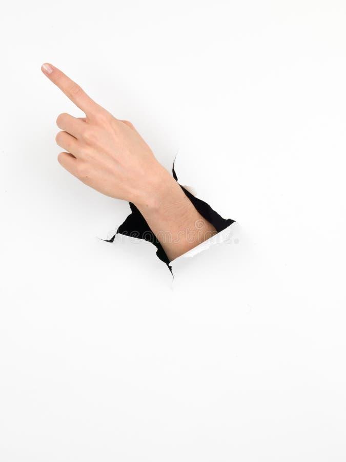 Weibliche Hand, die eine Richtung, Papier mit Loch anzeigt lizenzfreie stockfotos