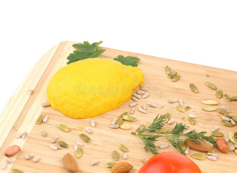 Nahaufnahme der Zitrone und der Nüsse auf Schneidebrett lizenzfreie stockbilder