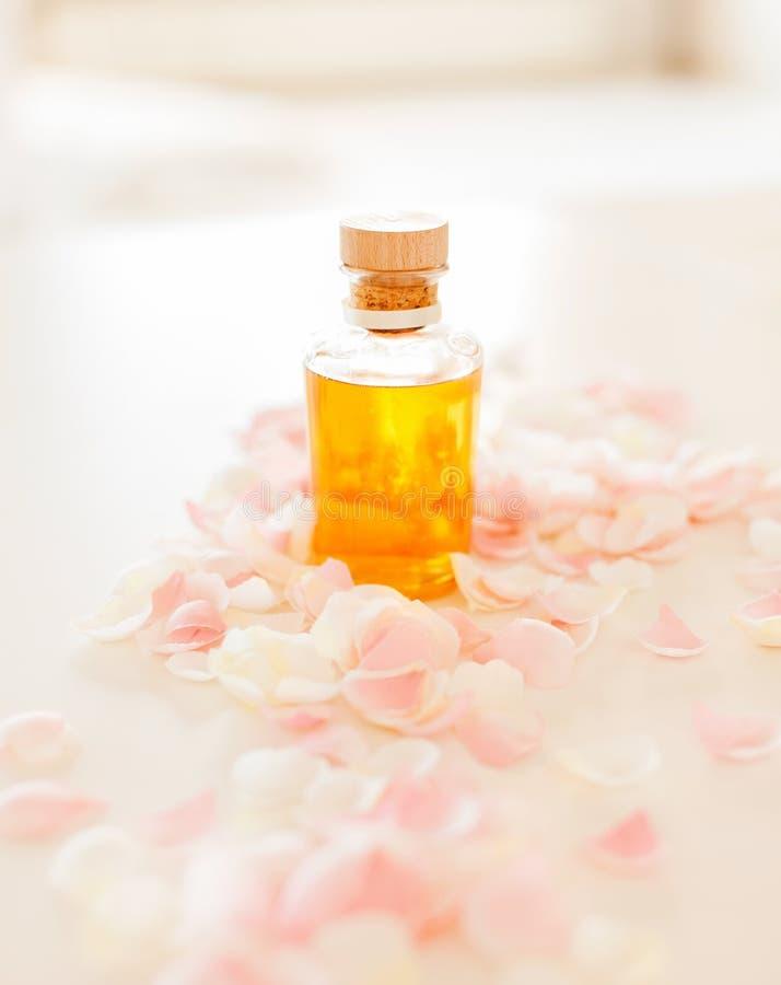 Nahaufnahme des ätherischen Öls und der rosafarbenen Blumenblätter stockbilder