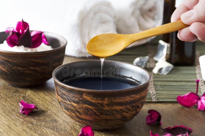Nahaufnahme des Öls für Massage in der Schüssel und in anderen kosmetischen Produkten Frau, die kosmetisches Öl für Schönheitsver lizenzfreie stockbilder