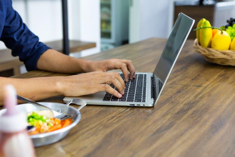 Nahaufnahme des Arbeitslaptops des jungen asiatischen Mannes, der Frühstück auf Holztisch isst stockfoto