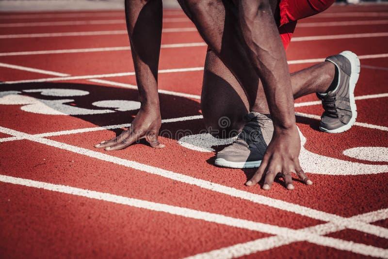 Nahaufnahme des Athlet ` s Hand- und Fußplanes drücken weg von der Bahn am Stadion stockfotos