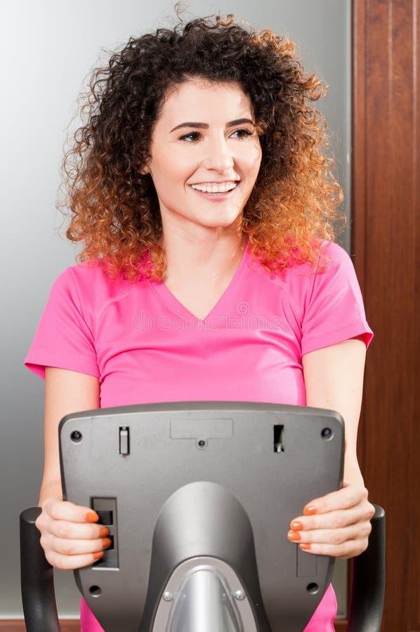 Nahaufnahme des attraktiven similing weiblichen Trainierens auf Stepper lizenzfreie stockbilder