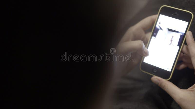 Nahaufnahme des aufpassenden Videos des Kerls am Telefon t?tigkeit Hände des Holdingtelefons des jungen Mannes mit Videotanzen Ta lizenzfreies stockbild