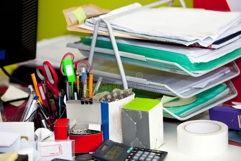 Nahaufnahme des aus dem wirklichem Leben unordentlichen Schreibtisches im Büro stockbild