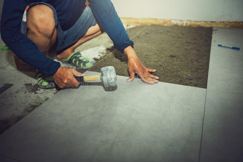 Nahaufnahme des Bauarbeiters installiert Fliesenpflasterung während unter Verwendung des Gummihammers zur Ausrichtung in Baustell stockfoto