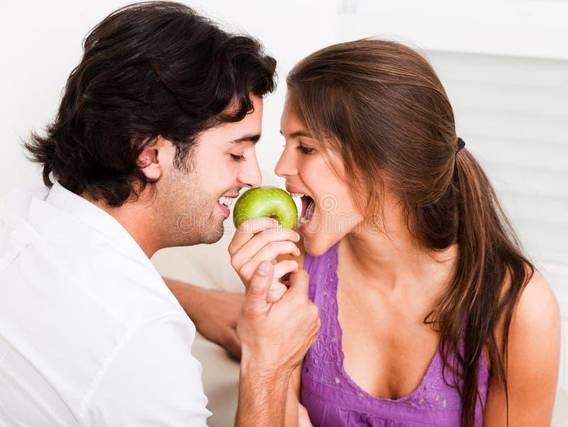 Nahaufnahme des beißenden grünen Apfels der jungen Paare stockbilder