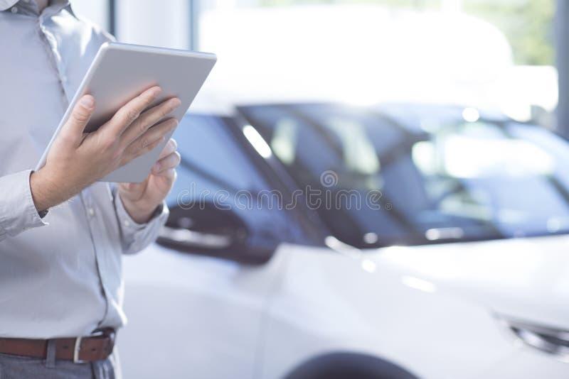 Nahaufnahme des Berufsautohändlers mit Tablette in einem Exklusiven lizenzfreie stockfotografie