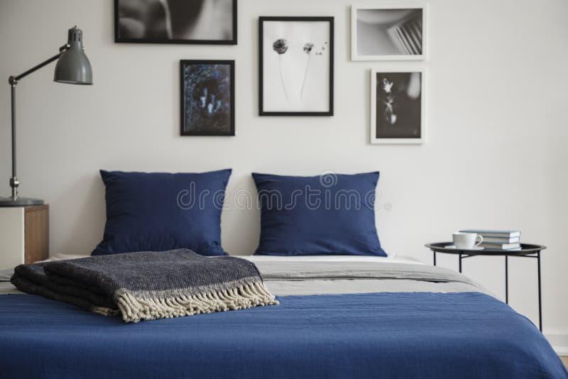 Nahaufnahme des Betts mit blauer Bettwäsche und Dunkelheit färbte Decke Nachttisch mit Büchern und Kaffee nahe bei ihm lizenzfreies stockbild