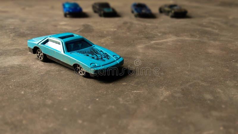 Nahaufnahme des blauen Spielzeugautos für Kinder auf verschiedenem Hintergrund mit verschiedenen Spielzeugautos auf Hintergrund stockbilder