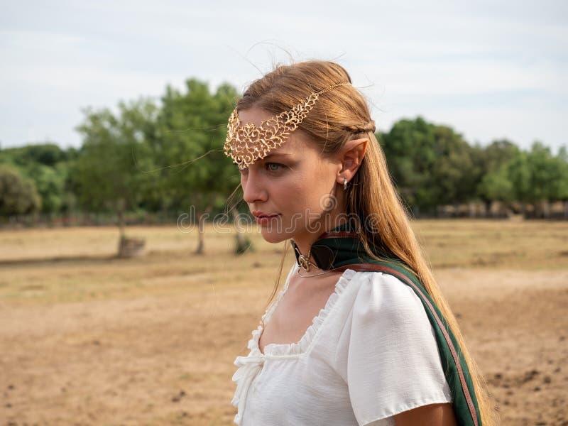 Nahaufnahme des blonden Mädchens mit blauen Augen und den Elfenohren, die ein grünes Kap tragen lizenzfreie stockfotos
