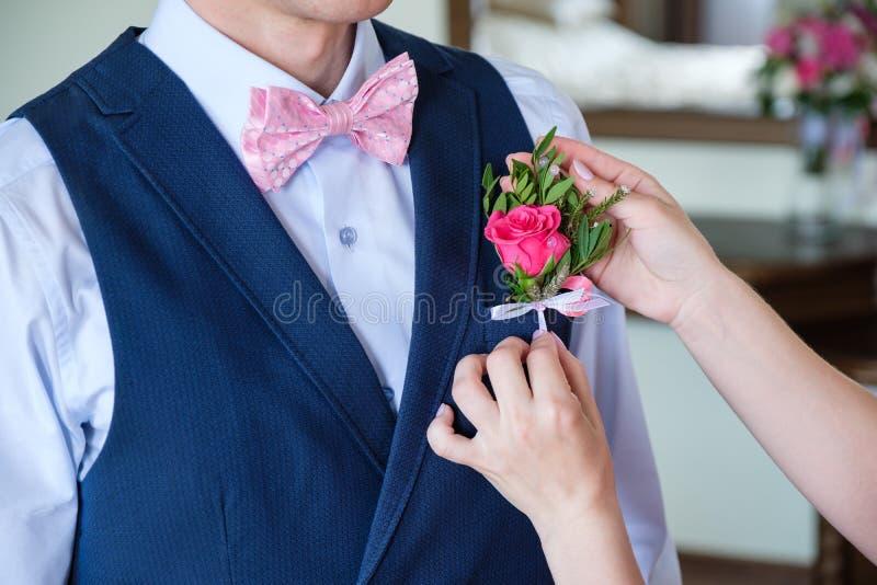 Nahaufnahme des Bräutigams im blauen Anzug, der einen rosa rosafarbenen Boutonniere zu einer Jacke im Raum feststeckt lizenzfreies stockfoto