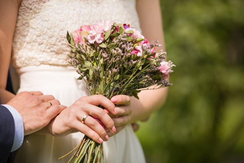 Nahaufnahme des Braut- und Bräutigamhändchenhaltens Wedding draußen Eben verheiratetes Paar - Hochzeitsdetails Gerade geheiratet lizenzfreies stockbild