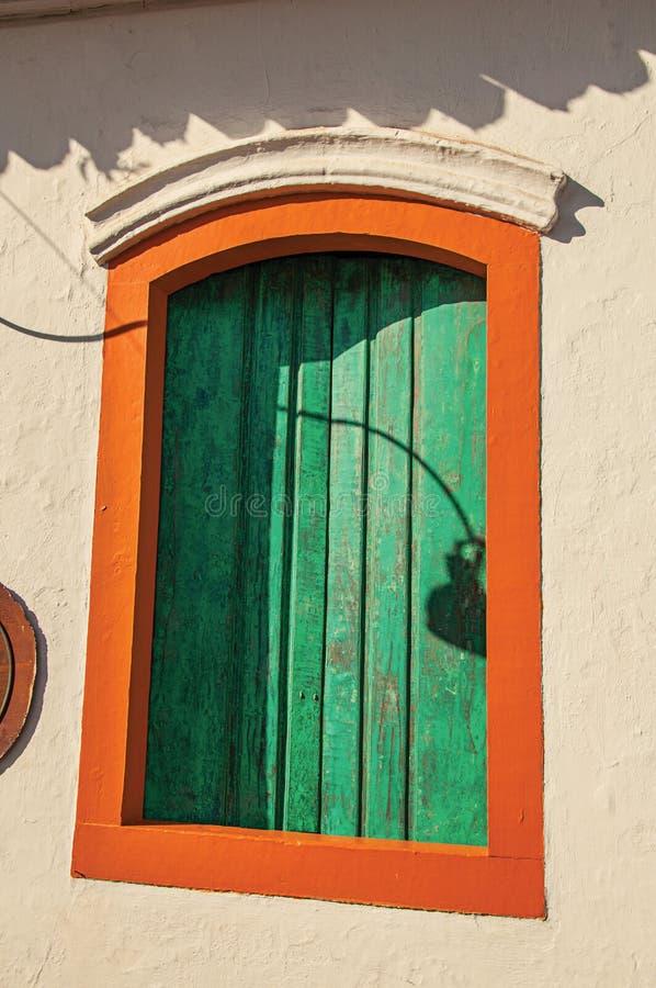 Nahaufnahme des bunten hölzernen Fensters mit geschlossenen Grünvorhängen in Paraty stockfotos