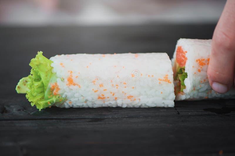 Nahaufnahme des Chefs übergibt das Rollen herauf Sushi stockbilder