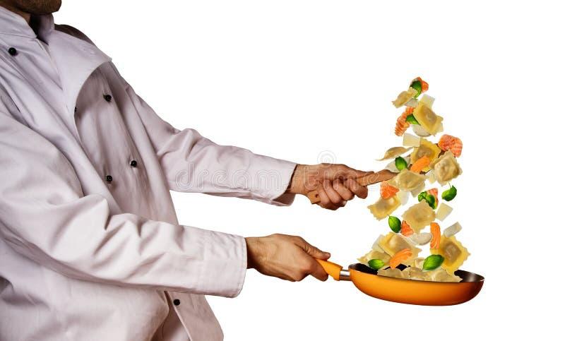 Nahaufnahme des Chefs italienische Teigwarenmahlzeit auf Weiß vorbereitend stockfotografie