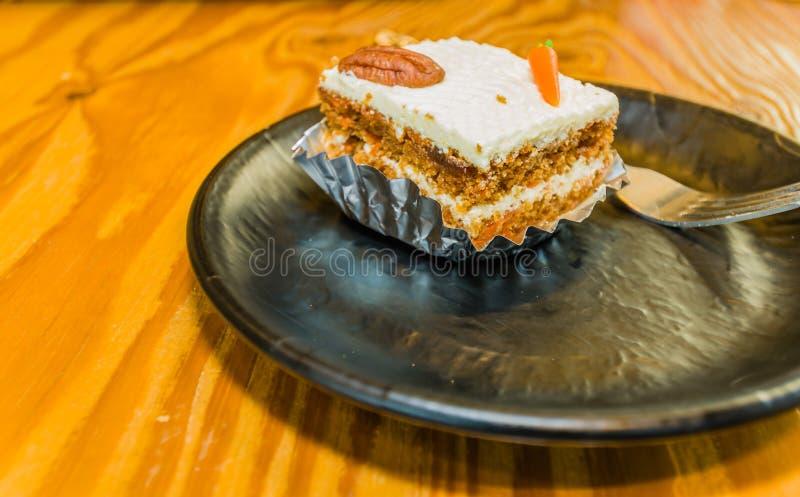 Nahaufnahme des Einzelstücks des Karottenkuchens verziert mit einer Pekannuss stockfotografie