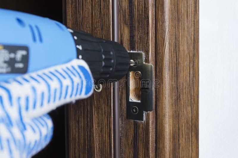 Nahaufnahme des elektrischen skrewdriver, männliche Hand in den Handschuhen mit ihr für die Reparatur eines Teils des Türgriffs,  stockbilder