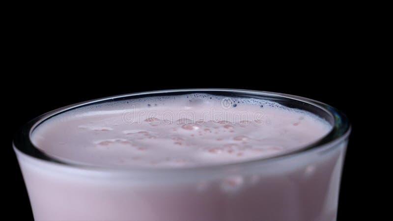 Nahaufnahme des Erdbeermilchshaken auf schwarzem lokalisiertem Hintergrund Feld Milchiges rosa Cocktail mit starkem Schaum und Bl stockfotografie